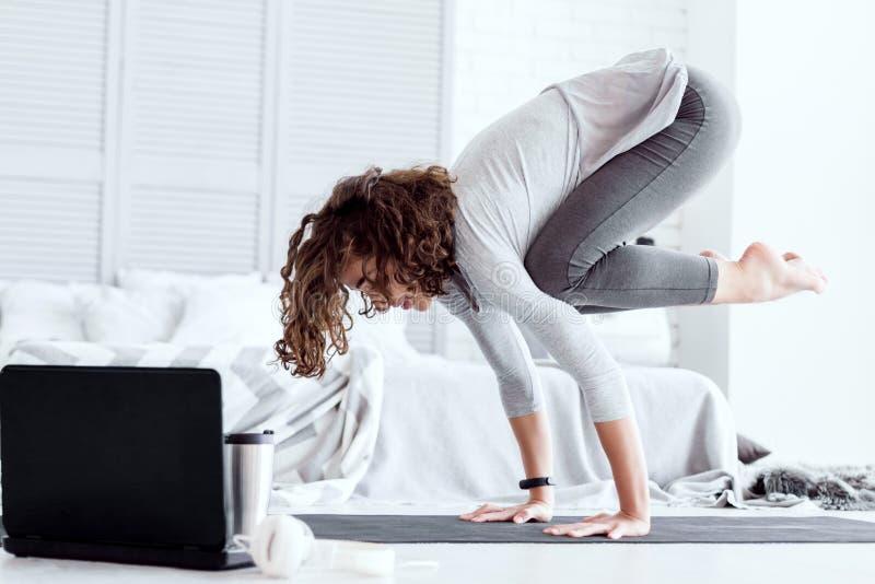 Erwachsene Frau, die zu Hause bakasana Yogahaltung tut lizenzfreies stockbild