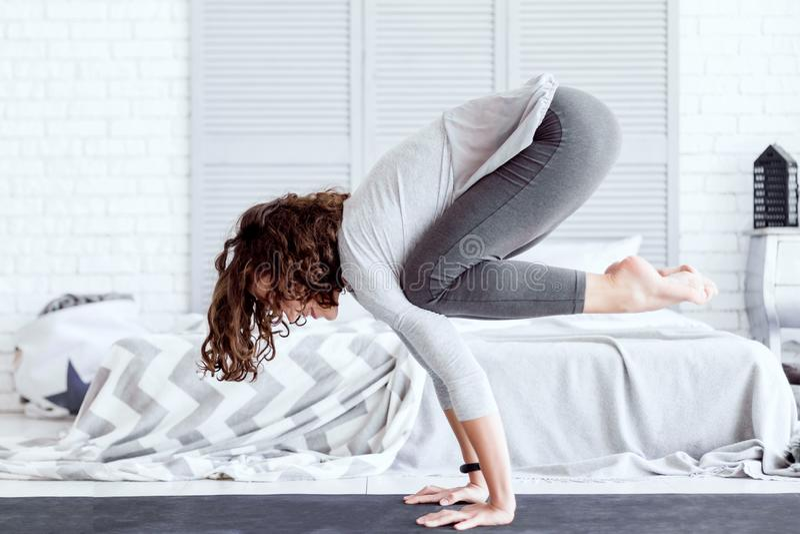 Erwachsene Frau, die zu Hause bakasana Yogahaltung tut lizenzfreies stockfoto