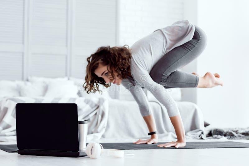 Erwachsene Frau, die zu Hause bakasana Yogahaltung tut stockbilder