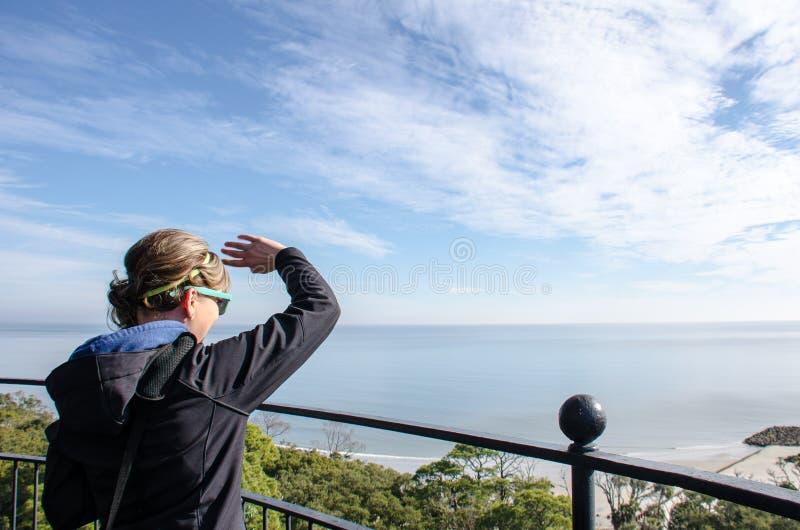 Erwachsene Frau genießt die Ansicht, nachdem sie die Spitze des Jagd-Insel-Leuchtturmes geklettert hat stockfoto