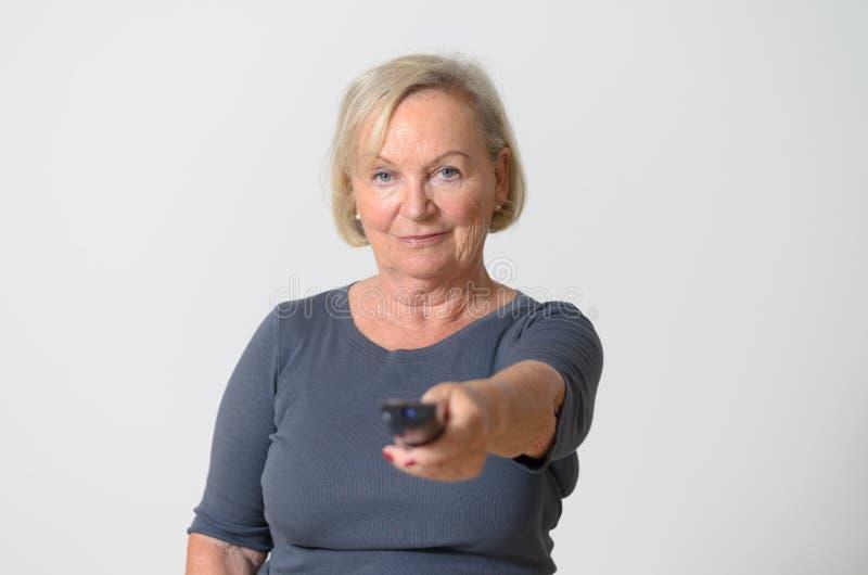 Erwachsene Frau halten Fernsteuerungs gegen Grau lizenzfreie stockbilder