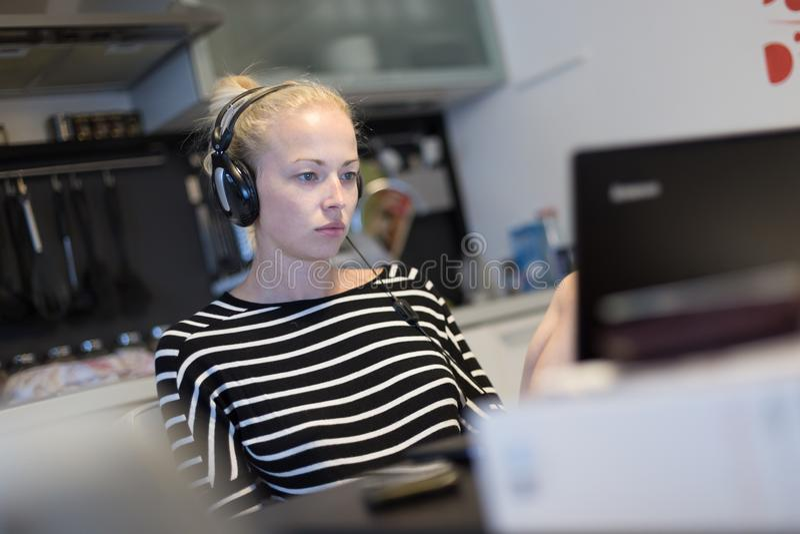Erwachsene Frau in ihrer zufälligen Haupt-Kleidung, die entfernt von ihrer kleinen Wohnung nachts arbeitet und spät studiert lizenzfreies stockbild