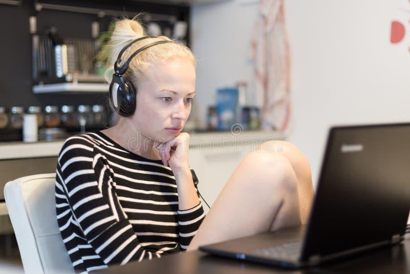 Erwachsene Frau in ihrer zufälligen Haupt-Kleidung, die entfernt von ihrer kleinen Wohnung nachts arbeitet und spät studiert lizenzfreie stockfotos
