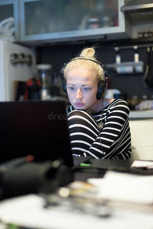 Erwachsene Frau in ihrer zufälligen Haupt-Kleidung, die entfernt von ihrer kleinen Wohnung nachts arbeitet und spät studiert lizenzfreies stockfoto