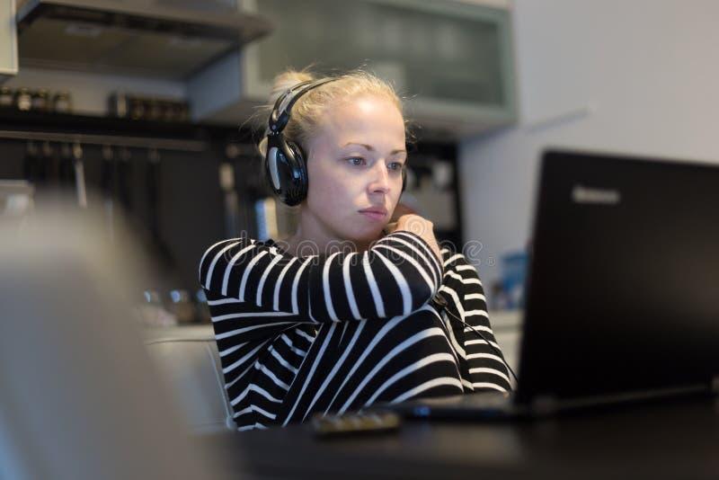 Erwachsene Frau in ihrer zufälligen Haupt-Kleidung, die entfernt von ihrer kleinen Wohnung nachts arbeitet und spät studiert lizenzfreie stockfotografie