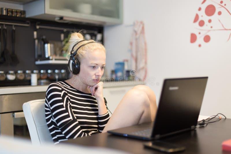 Erwachsene Frau in ihrer zufälligen Haupt-Kleidung, die entfernt von ihrer kleinen Wohnung nachts arbeitet und spät studiert stockfotos