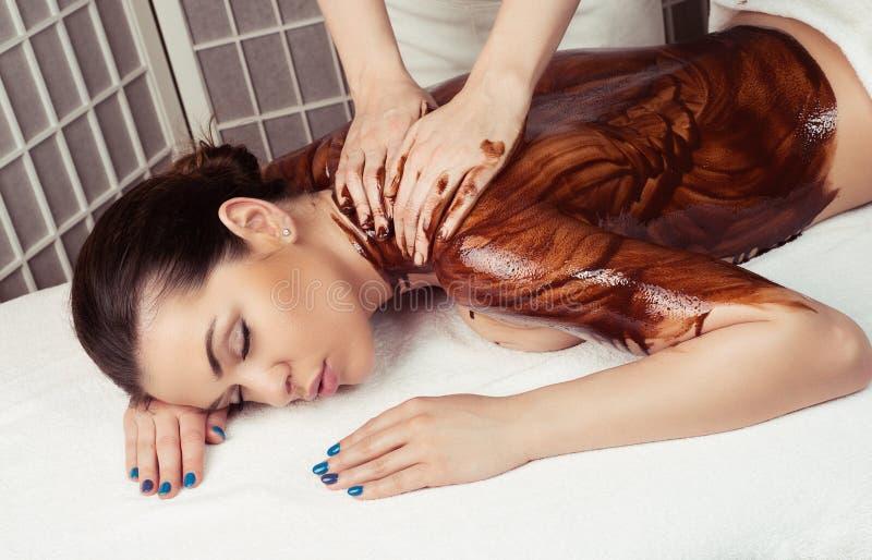 Erwachsene Frau im Badekurortsalon, der die entspannende Massage des Körpers, an liegend hat stockbilder