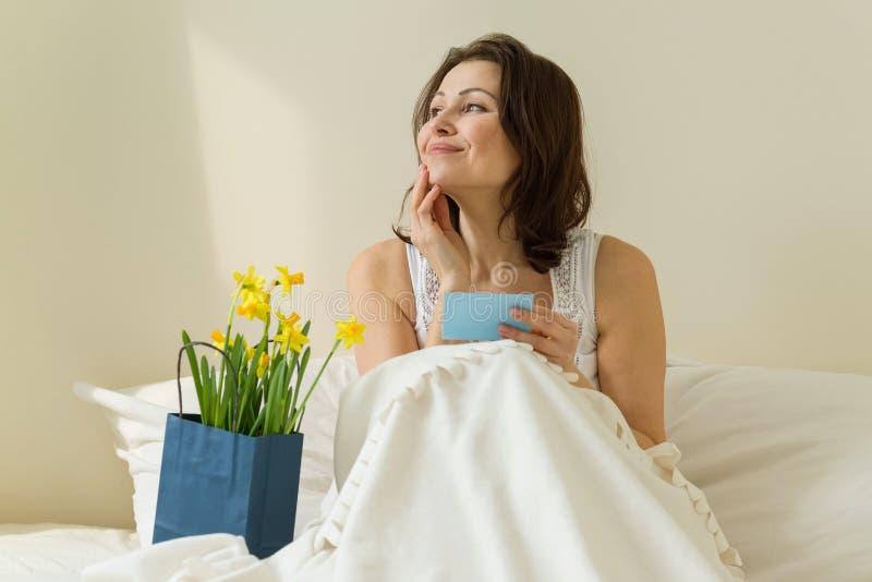 Erwachsene Frau im Bett zu Hause, Morgen empfing einen Überraschungsblumenstrauß von Blumen Liest Karte und glücklich lizenzfreie stockbilder