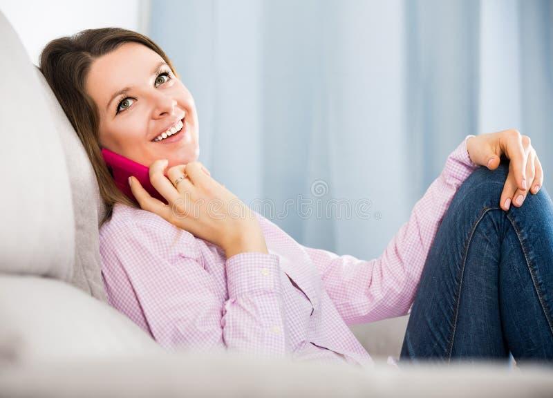 Erwachsene Frau ist, sitzend und mit ihrem Telefon stockfotografie