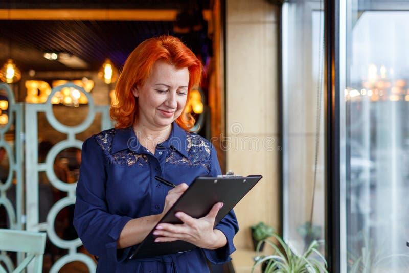 Erwachsene Frau mit dem roten Haar, Griffe ein Klemmbrett und schreibt etwas stockfotografie