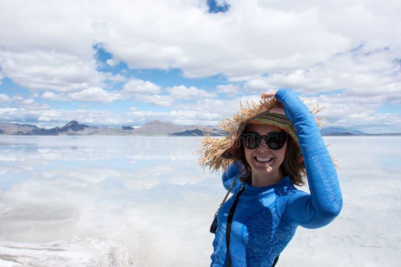Erwachsene Frau trägt einen Strohhut, der an den Bonneville-Salz-Ebenen in West-Utah aufwirft stockfotografie