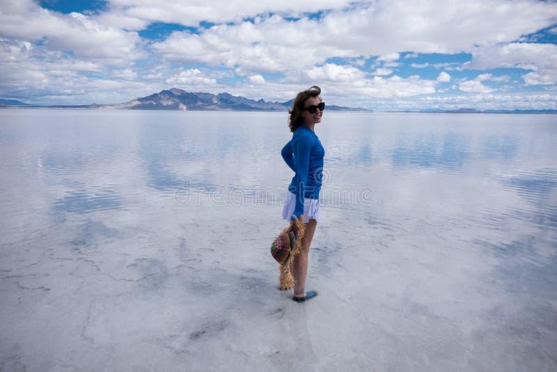Erwachsene Frau trägt einen Strohhut, der an den Bonneville-Salz-Ebenen in West-Utah aufwirft lizenzfreie stockfotografie