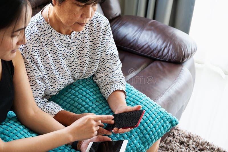 Erwachsene Frau und Tochter, die Smartphone mit leerem Bildschirm verwendet Frau, die auf Handyanzeige zeigt lizenzfreie stockfotos