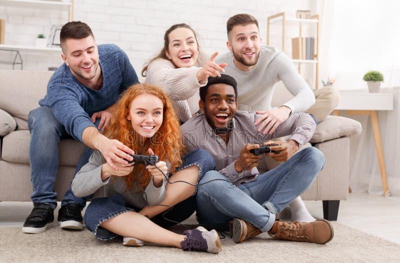 Erwachsene Freunde, welche die Videospiele, zu Hause sitzend auf Boden spielen stockfotografie