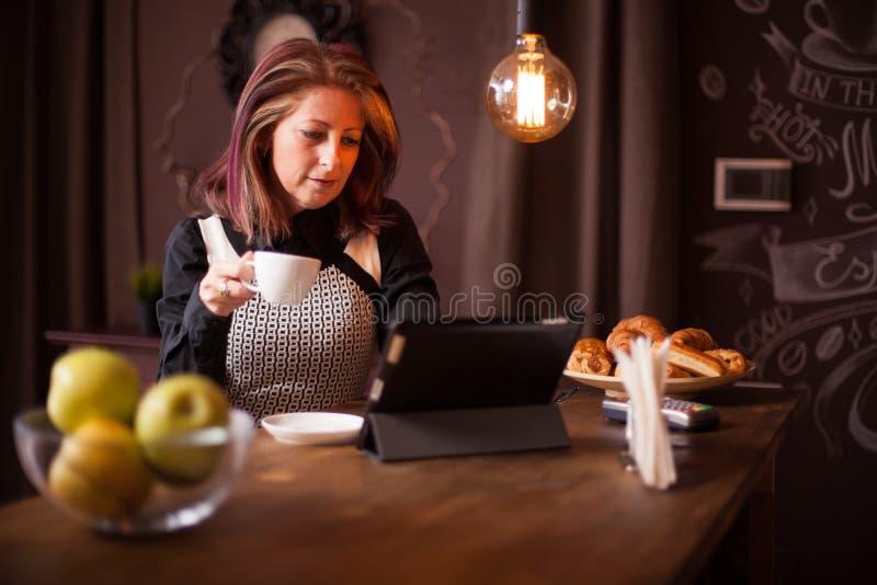 Erwachsene Geschäftsfrau, die auf ihrer Tablette in einer Weinlesekaffeestube sucht stockfoto