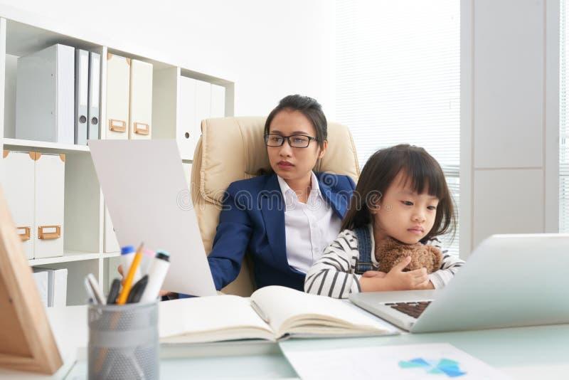 Erwachsene Geschäftsfrau, die mit Kind auf Knien arbeitet stockfotos
