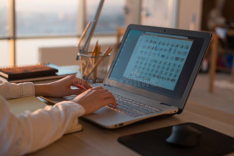 Erwachsene Geschäftsfrau, die zu Hause unter Verwendung des Computers, Geschäftsideen auf einem PC-Schirm online studierend arbei stockfoto