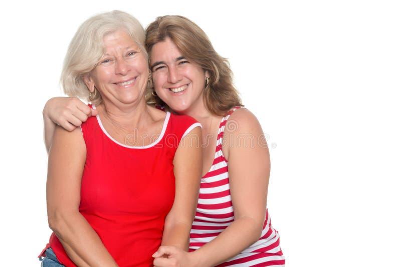 Erwachsene hispanische Frau, die ihre ältere Mutter umarmt stockfotos