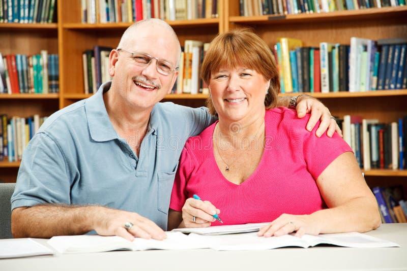 Erwachsene Kursteilnehmer in der Bibliothek lizenzfreie stockfotos