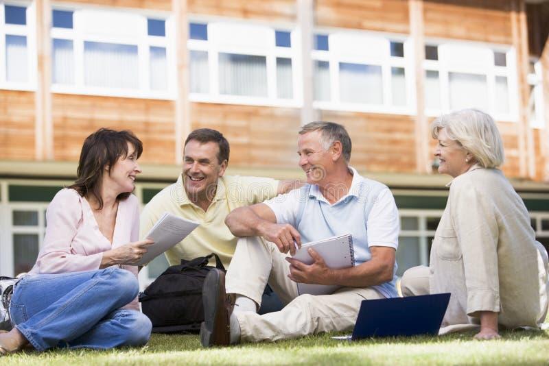 Erwachsene Kursteilnehmer, die auf einem Campusrasen sitzen stockbild