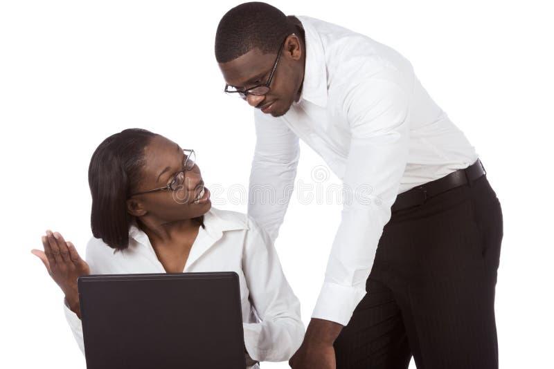 Erwachsene Kursteilnehmerpaare des Afroamerikaners durch Laptop lizenzfreie stockfotos