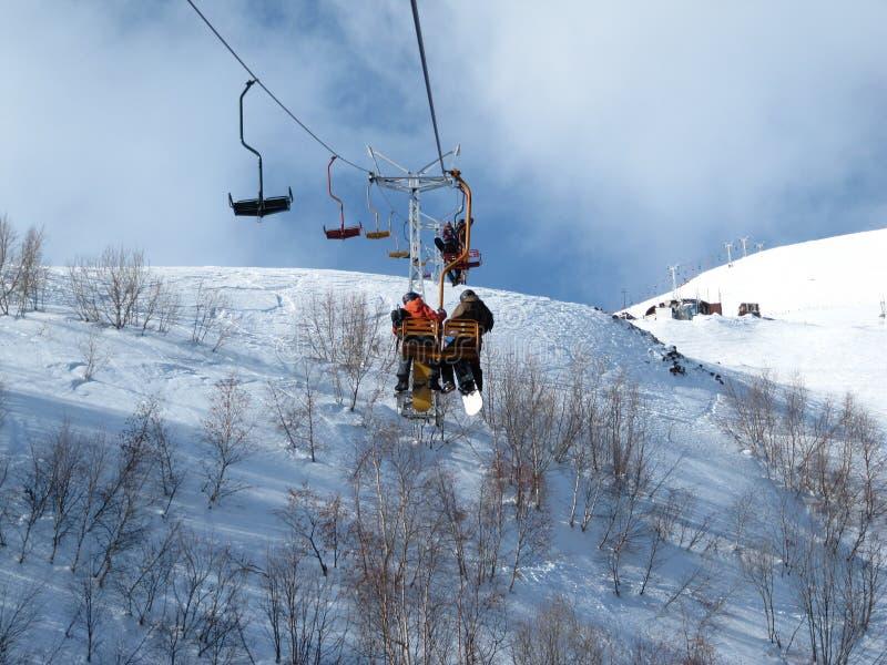 Erwachsene Leute der Paare sitzen in Winterskiortsessellift-Griff Snowboards in den Händen und in den Bewegungen, vom Berg zu übe stockfoto