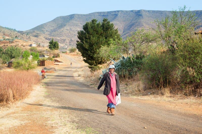 Erwachsene lustige lächelnde afrikanische Frau im hellen Kleid auf authentischer Dorfstraße, alte glückliche lachende Basothofrau stockbild