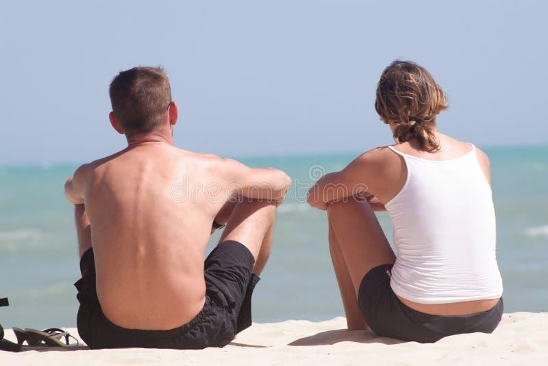 Erwachsene Paare, die auf dem Strand sitzen lizenzfreie stockbilder