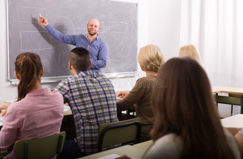 Erwachsene Studenten mit Lehrer im Klassenzimmer stockbild