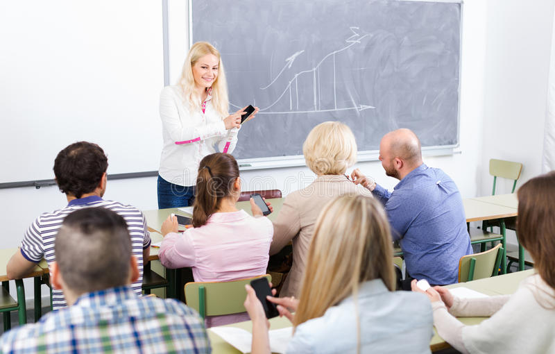 Erwachsene Studenten mit Smartphones im Klassenzimmer stockbild