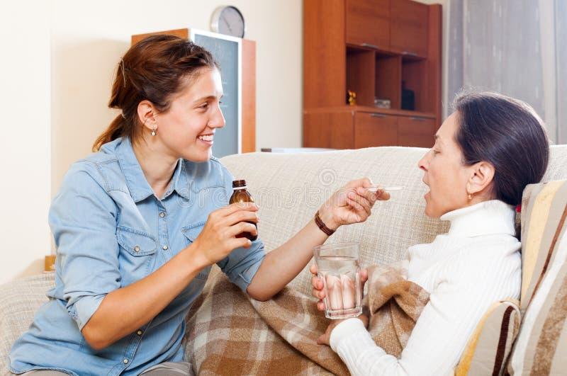 Erwachsene Tochter, die der Mutter den flüssigen Medikament gibt stockfoto