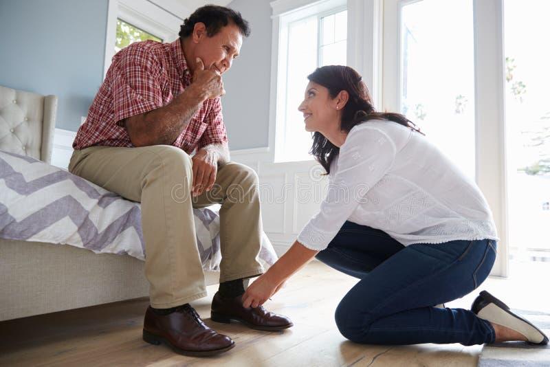 Erwachsene Tochter hilft Vater Suffering With Dementia anzukleiden lizenzfreie stockfotos
