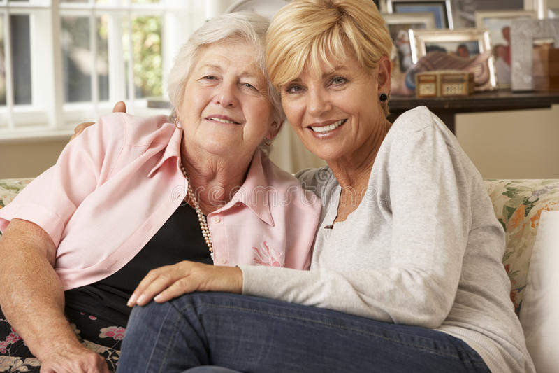 Erwachsene Tochter, welche die ältere Mutter sitzt auf Sofa At Home besucht stockbild
