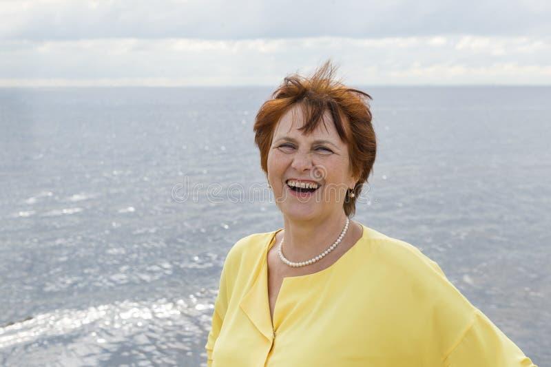 Erwachsene weiße Frau auf dem Strand lachend, Porträt von ältere Personen lizenzfreie stockfotos