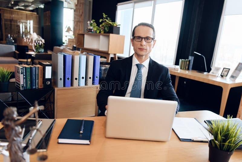 Erwachsener überzeugter Mann in der Klage sitzt bei Tisch im Büro Rechtsanwalt ist bei der Arbeit stockfoto