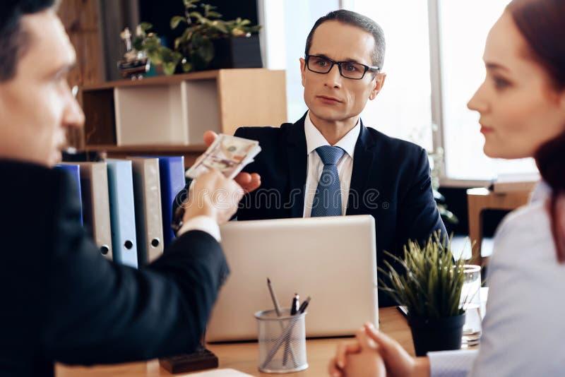 Erwachsener überzeugter Mann gibt dem Rechtsanwalt für Scheidung Geld und sitzt am Bürotisch stockfoto