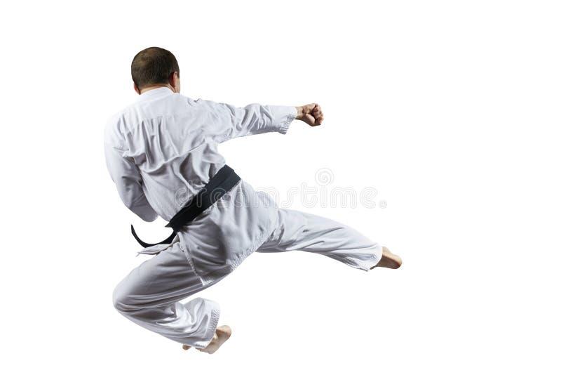 Erwachsener Athlet bildet einen Tritt in einem Sprung gegen einen weißen lokalisierten Hintergrund aus stockfotos