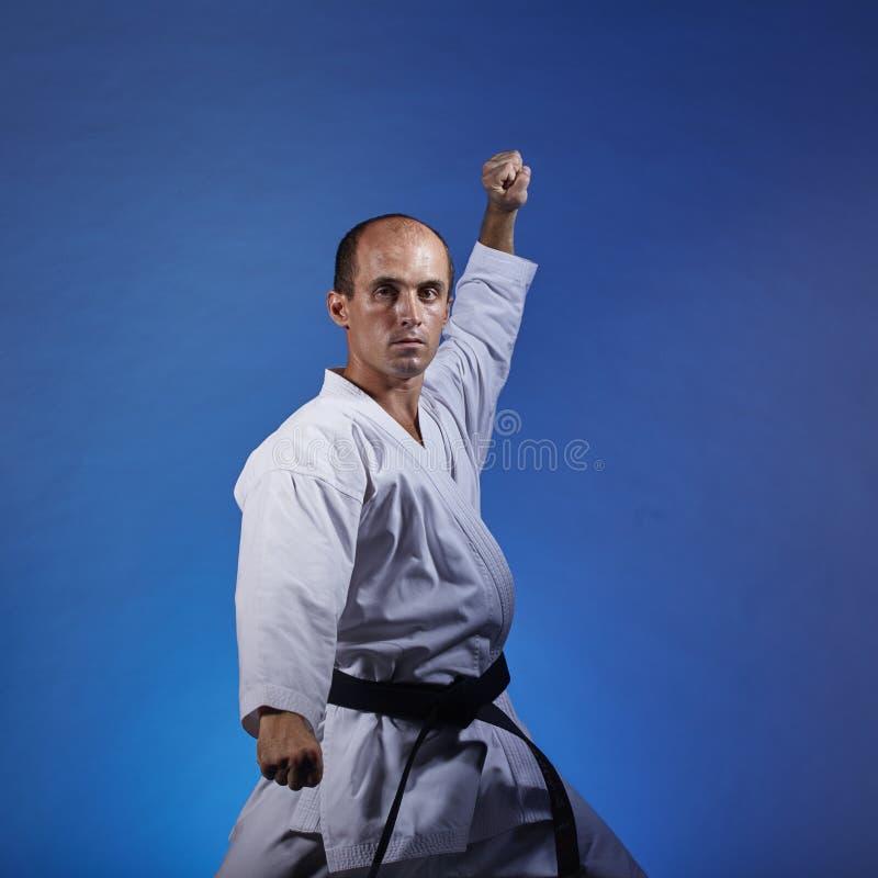 Erwachsener Athlet, der eine formale Karateübung auf einem blauen Hintergrund trainiert lizenzfreies stockbild