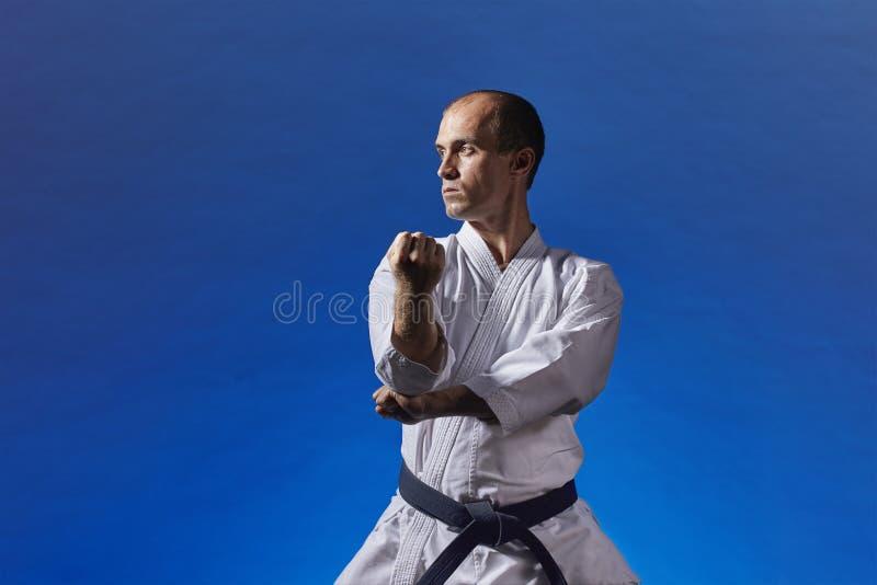 Erwachsener Athlet führt formale Karateübungen auf einem blauen Hintergrund durch lizenzfreie stockbilder