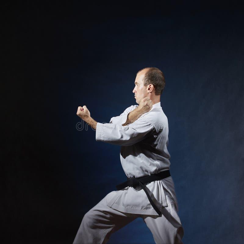 Erwachsener Athlet führt formale Karateübungen im weißen karategi durch lizenzfreie stockfotografie
