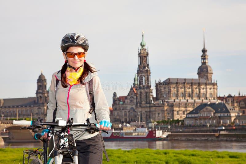 Erwachsener attraktiver weiblicher Radfahrer, der vor dem hintergrund aufwirft stockfoto