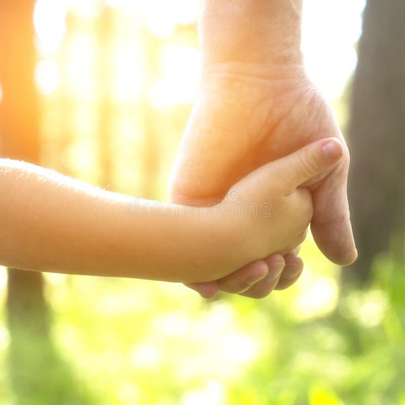 Erwachsener, der eine Kinderhand, Nahaufnahmehände hält stockfotografie