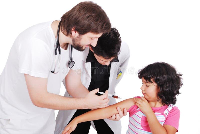 Erwachsener Doktor, der dem weiblichen Patienten Einspritzung gibt, während Student aufpasst stockfotos