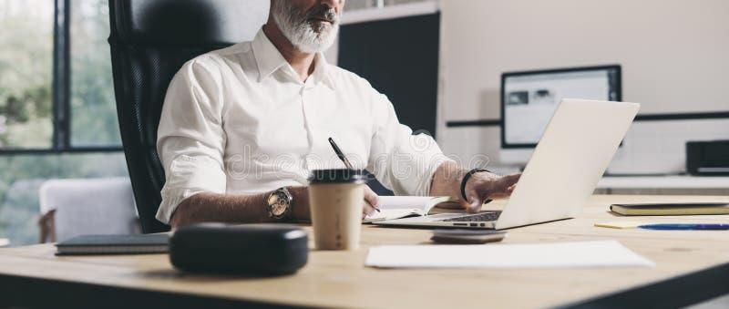 Erwachsener Geschäftsmann, der im modernen coworking Büro arbeitet Überzeugter Mann, der zeitgenössischen mobilen Laptop verwende lizenzfreie stockfotos
