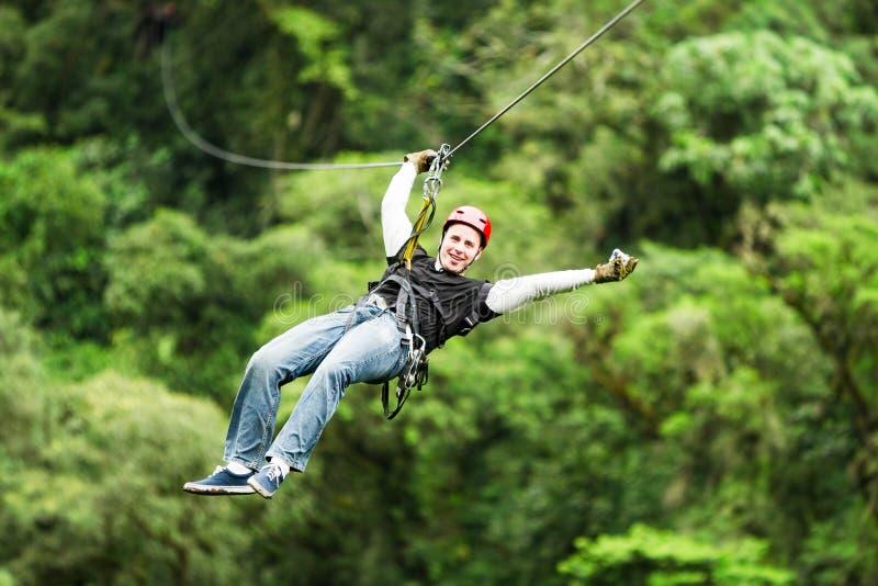 Erwachsener Mann auf Ziplinie gegen unscharfen Wald lizenzfreie stockbilder