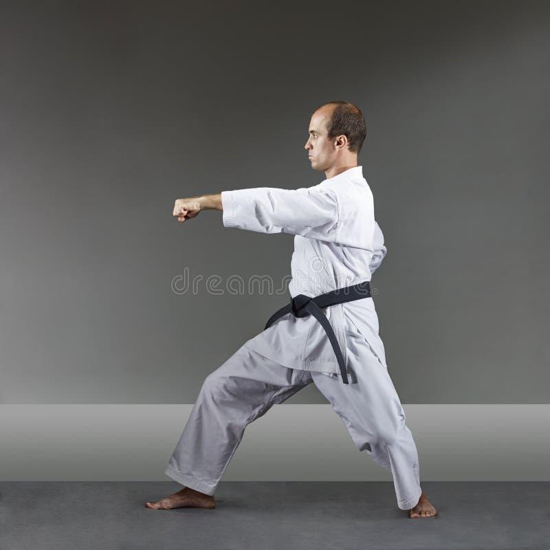 Erwachsener Mann bildet formale Karateübungen auf einem grauen Hintergrund aus lizenzfreie stockfotos