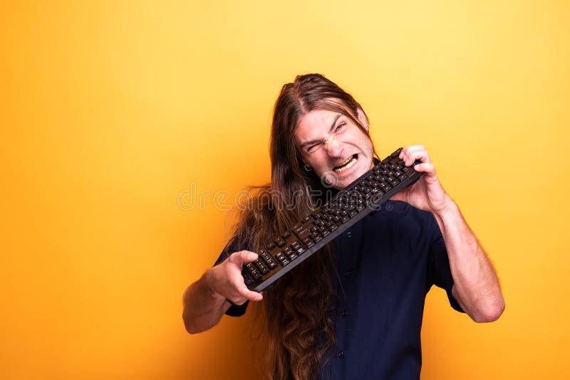 Erwachsener Mann, der lustige Gesichter mit Tastatur macht lizenzfreie stockfotos