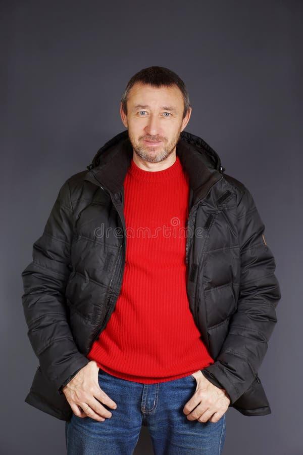 Erwachsener Mann, der schwarze Jacke und rote Strickjacke trägt stockbild