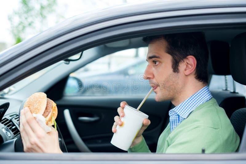 Erwachsener Mann, der sein Auto beim Essen des Lebensmittels im Verkehr fährt lizenzfreies stockbild