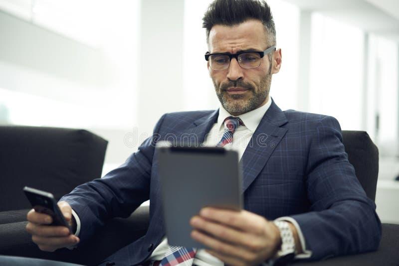 Erwachsener Mann in einer Jacke und in den Gläsern im Büro, damit Online-Bankings-Service Bargeschäft vereinfacht lizenzfreies stockfoto